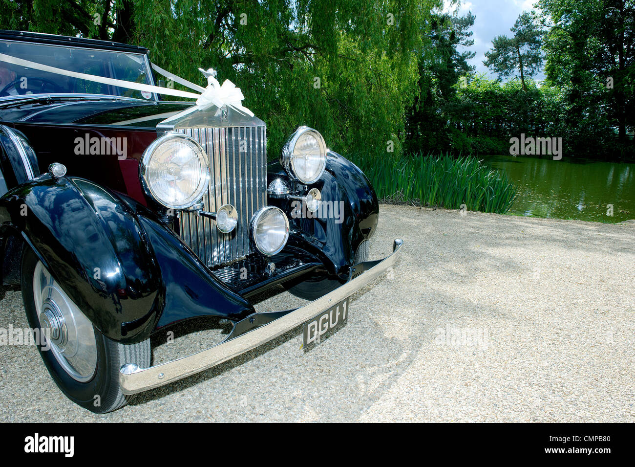 old fashioned vintage wedding car vehicle with white ribbons parked ...