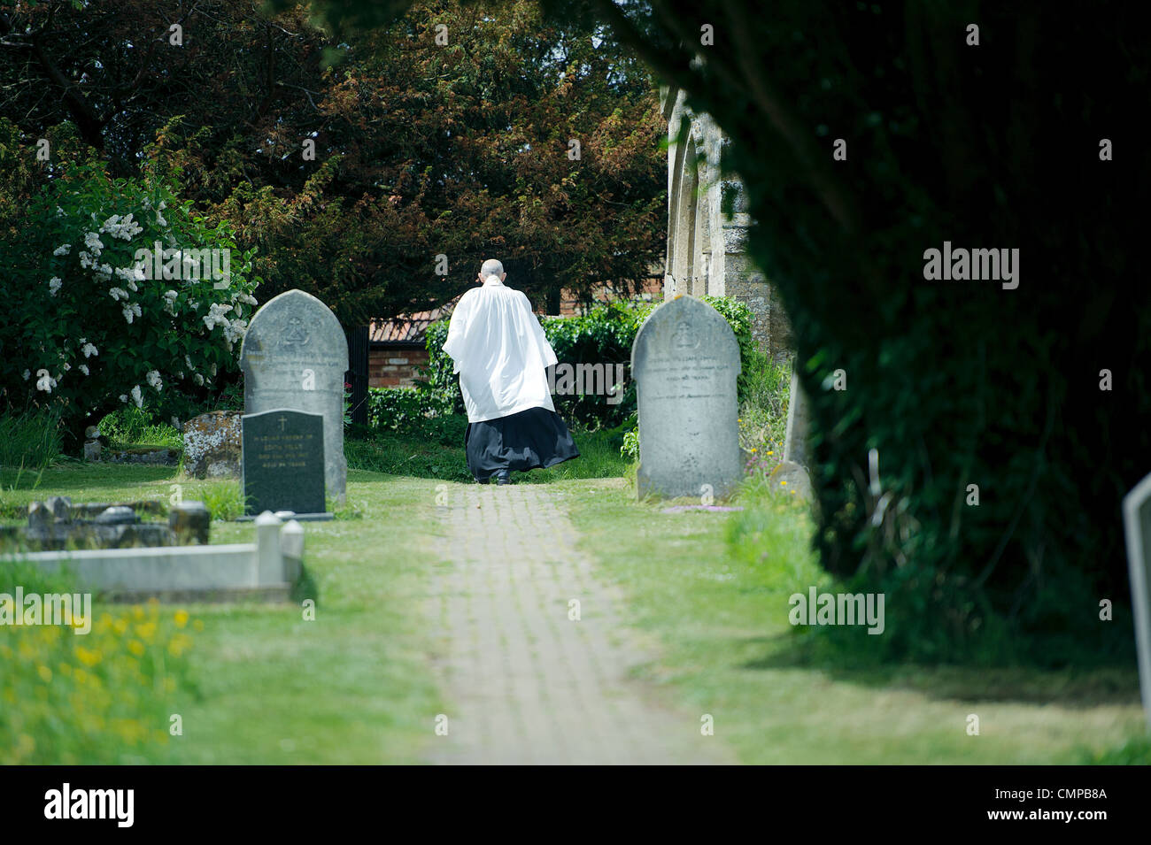 back of vicar walking towards church through graveyard past gravestones - Stock Image