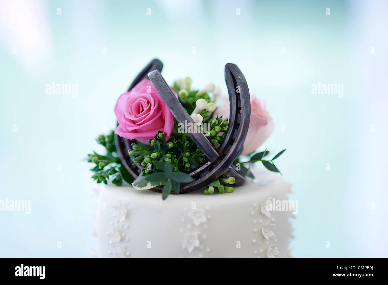 top tier of white wedding cake with pink rose and horseshoe - Stock Image