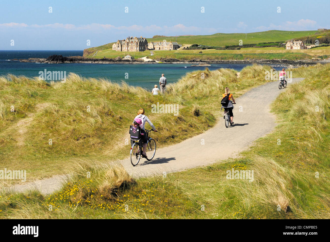Cycling the Runkerry Trail to the Giants Causeway at Portballintrae strand near Bushmills and Portrush, Northern - Stock Image