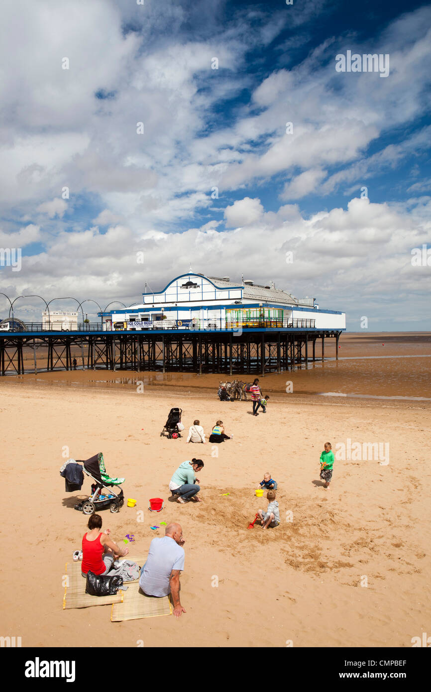 UK, England, Lincolnshire, Cleethorpes, families relaxing on beach near pier in summer sunshine - Stock Image