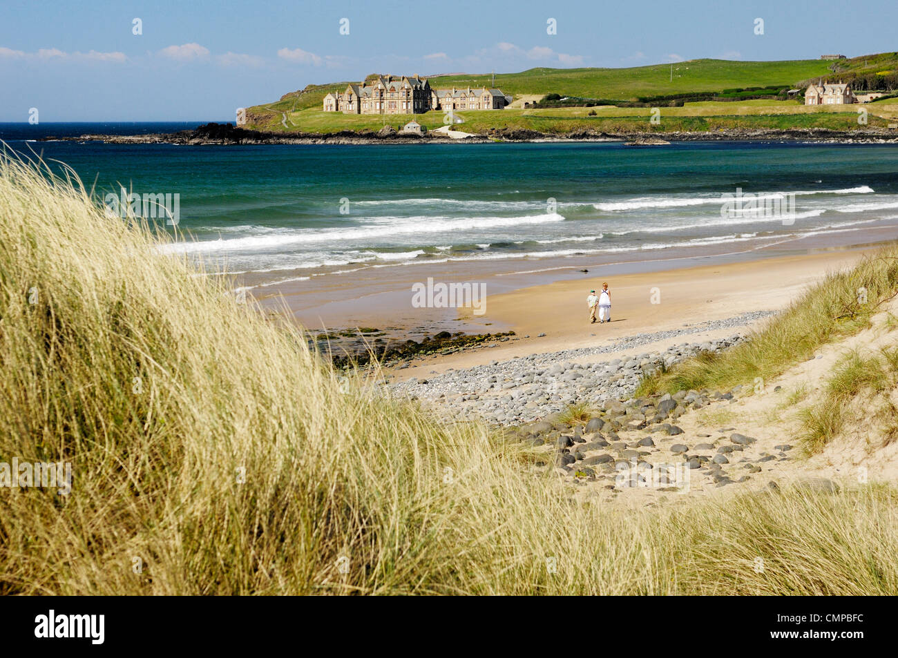 Woman and boy walking on Runkerry Strand seen from Runkerry Trail, Portballintrae near Bushmills , Northern Ireland - Stock Image