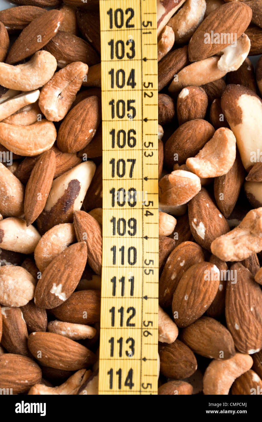 Mixed nuts and measure tape - Stock Image