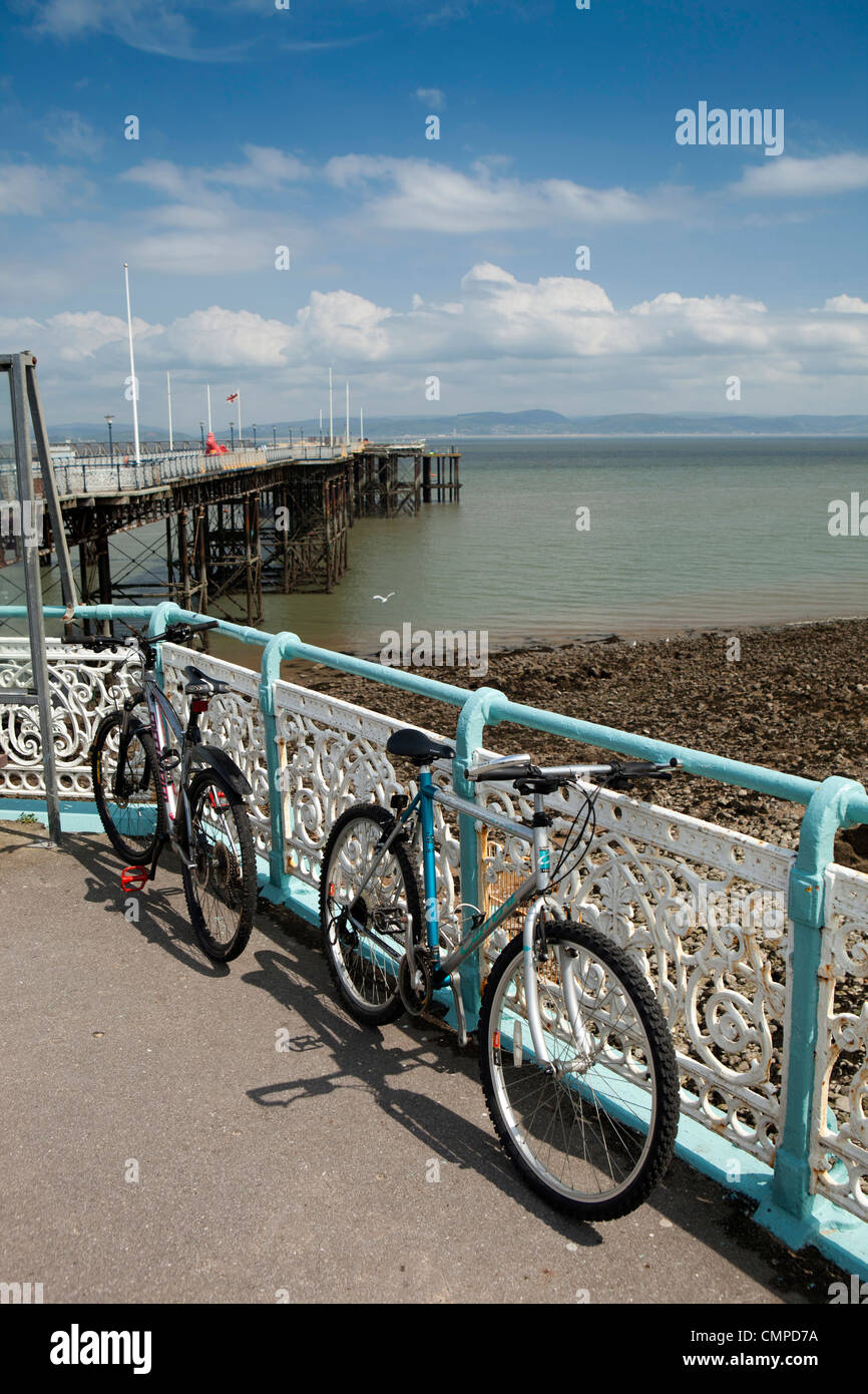 UK, Wales, Swansea, Mumbles Pier, two bicycles leaning against the cast iron railings - Stock Image