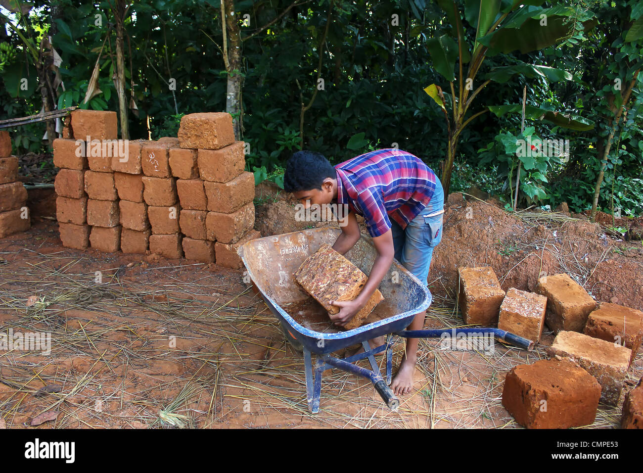 young boy turning bricks in a brick factory india,poverty child labour,homeless people - Stock Image
