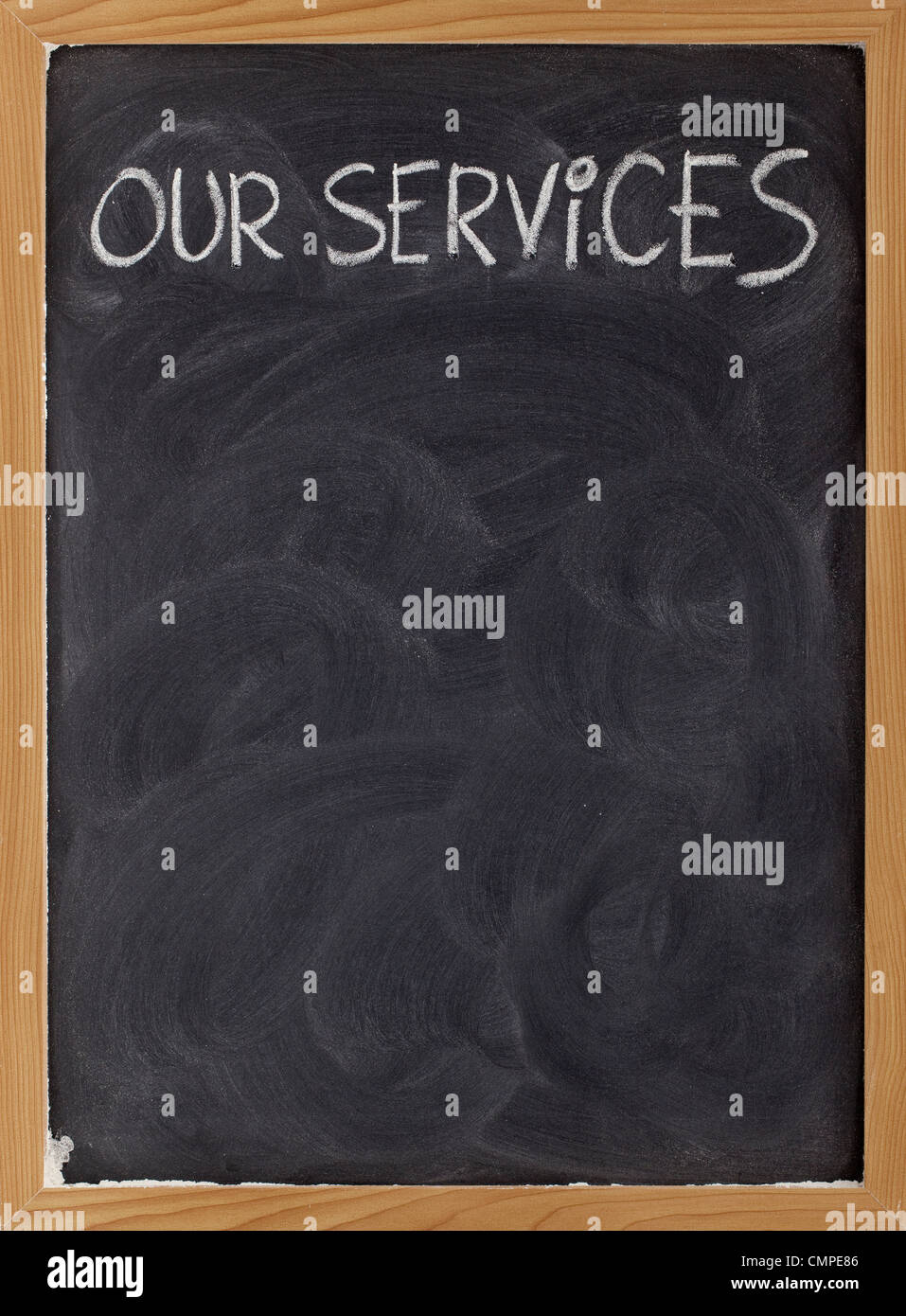 our services - white chalk handwriting on blackboard with eraser smudges, copy space below - Stock Image