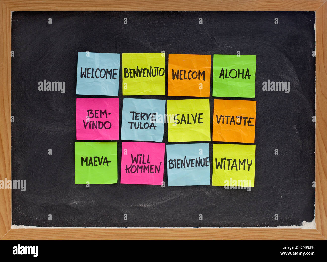 welcome in a dozen of languages - array of colorful sticky notes on blackboard with white chalk texture - Stock Image