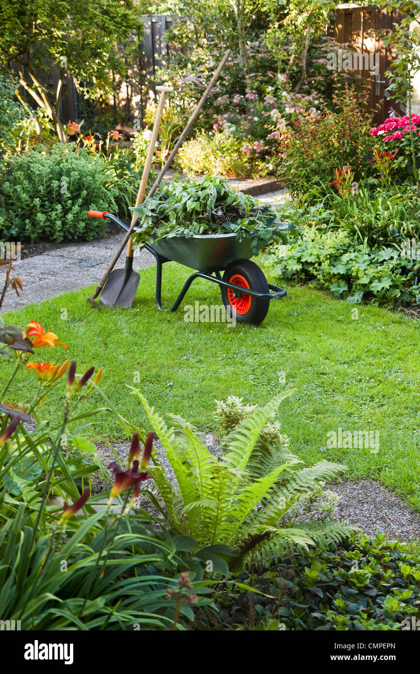 Evening after work in summer garden with wheelbarrow, shovel and rake - vertical - Stock Image