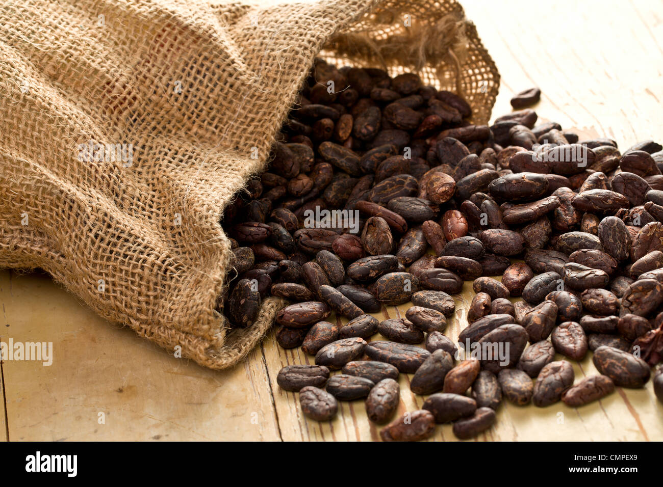 the jute bag with cocoa beans on wooden table - Stock Image