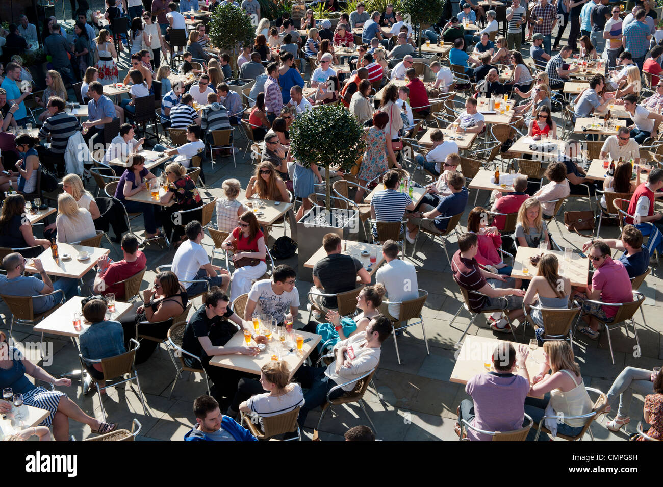 Revellers enjoy the evening sunshine in a beer garden in Castlefield in Manchester (Editorial use only). - Stock Image