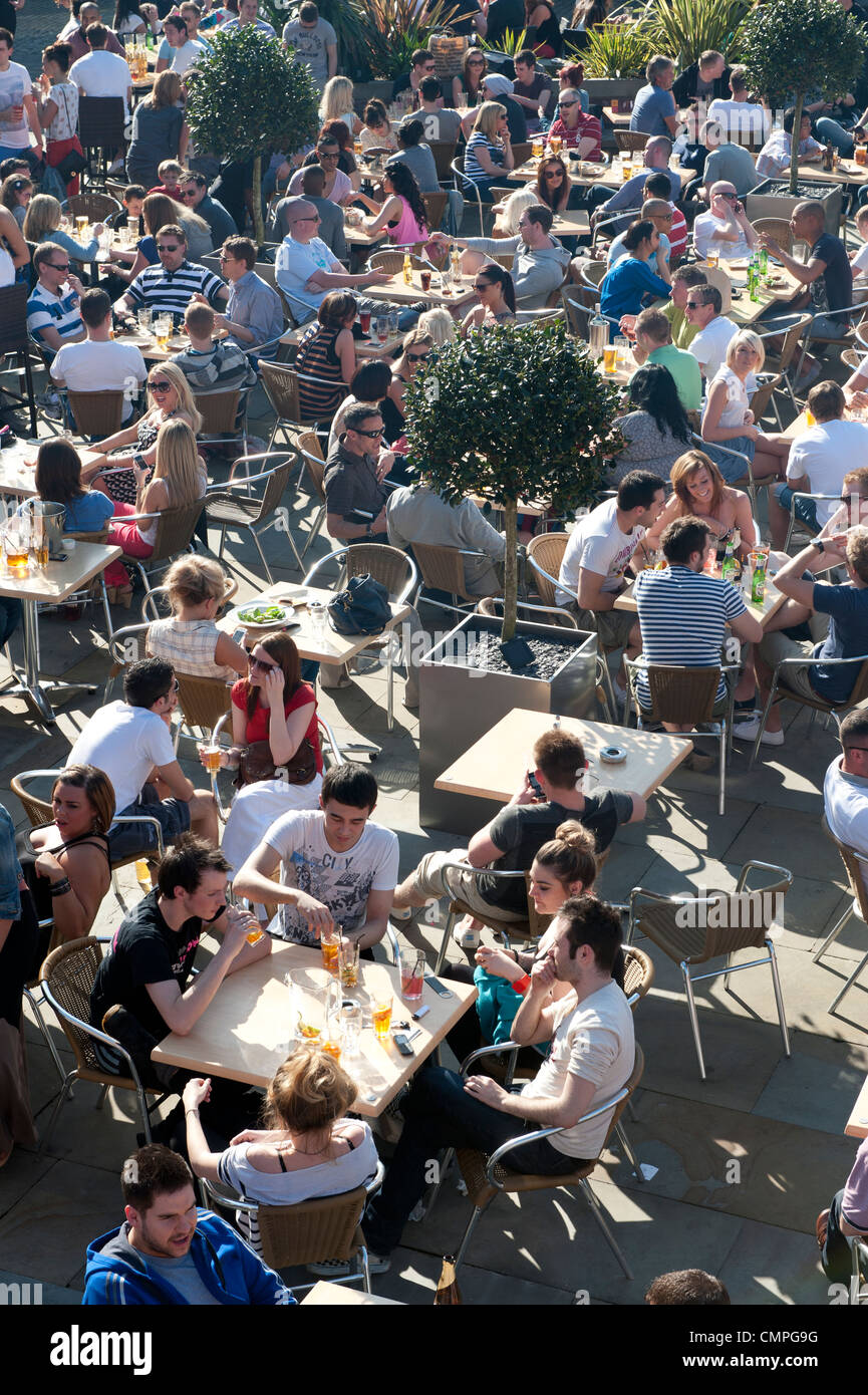 Revellers enjoy the evening sunshine in a beer garden in Castlefield in Manchester. - Stock Image