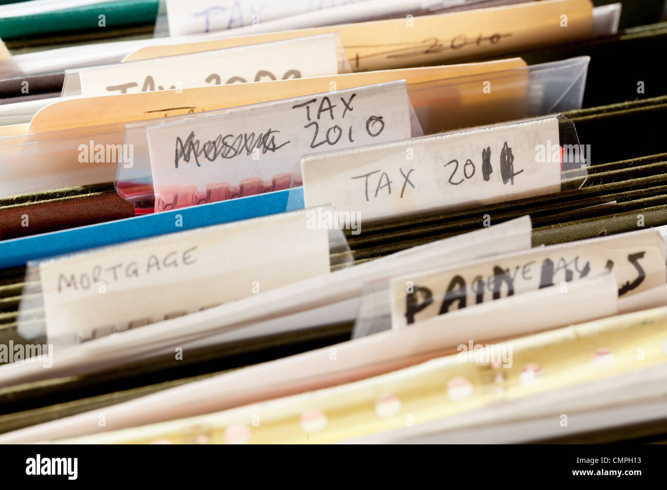 Paperwork folders in file drawer sorted into tax years and mortgage documents - Stock Image