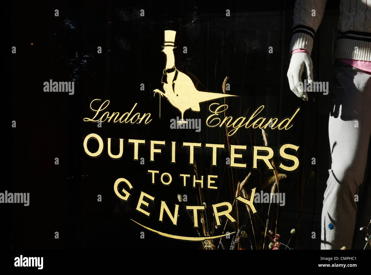 A sign in a shop window that  reads 'Outfitters to the Gentry' - Stock Image
