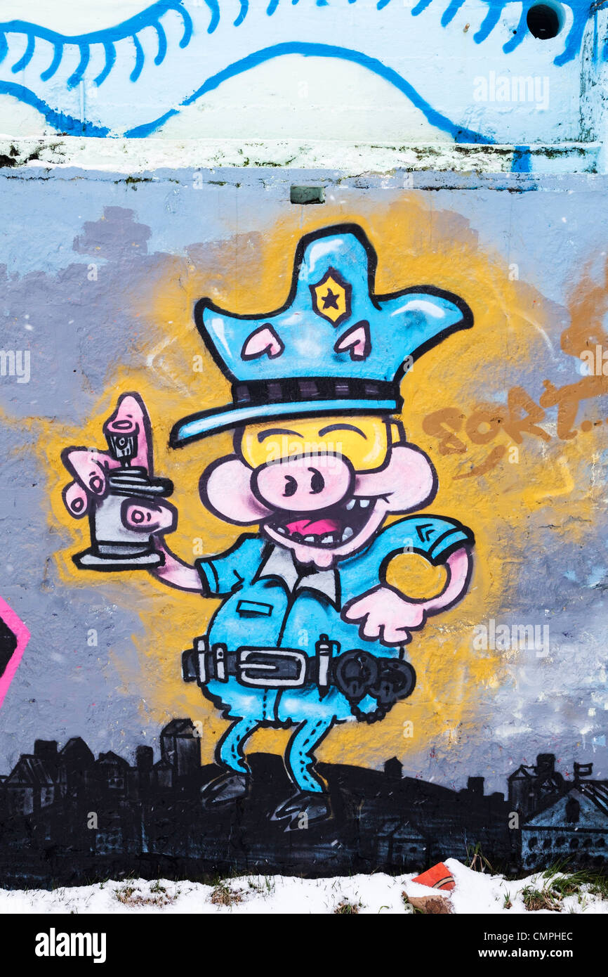 Graffiti, picture of a laughing pig dressed as a policeman with spray, on a wall in Reykjavik, Iceland - Stock Image