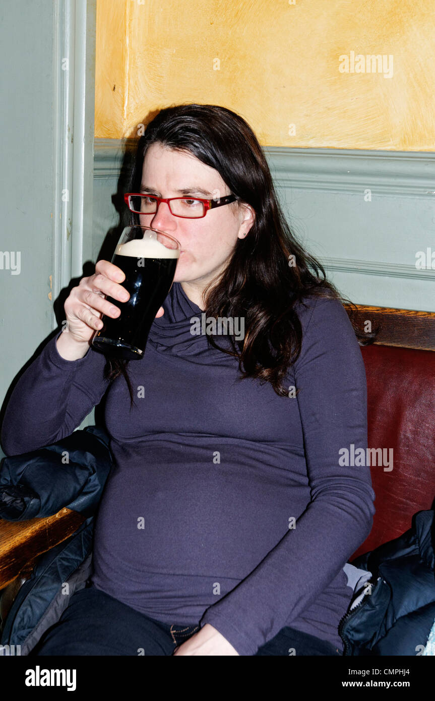 A pregnant woman drinking a pint in a pub - Stock Image