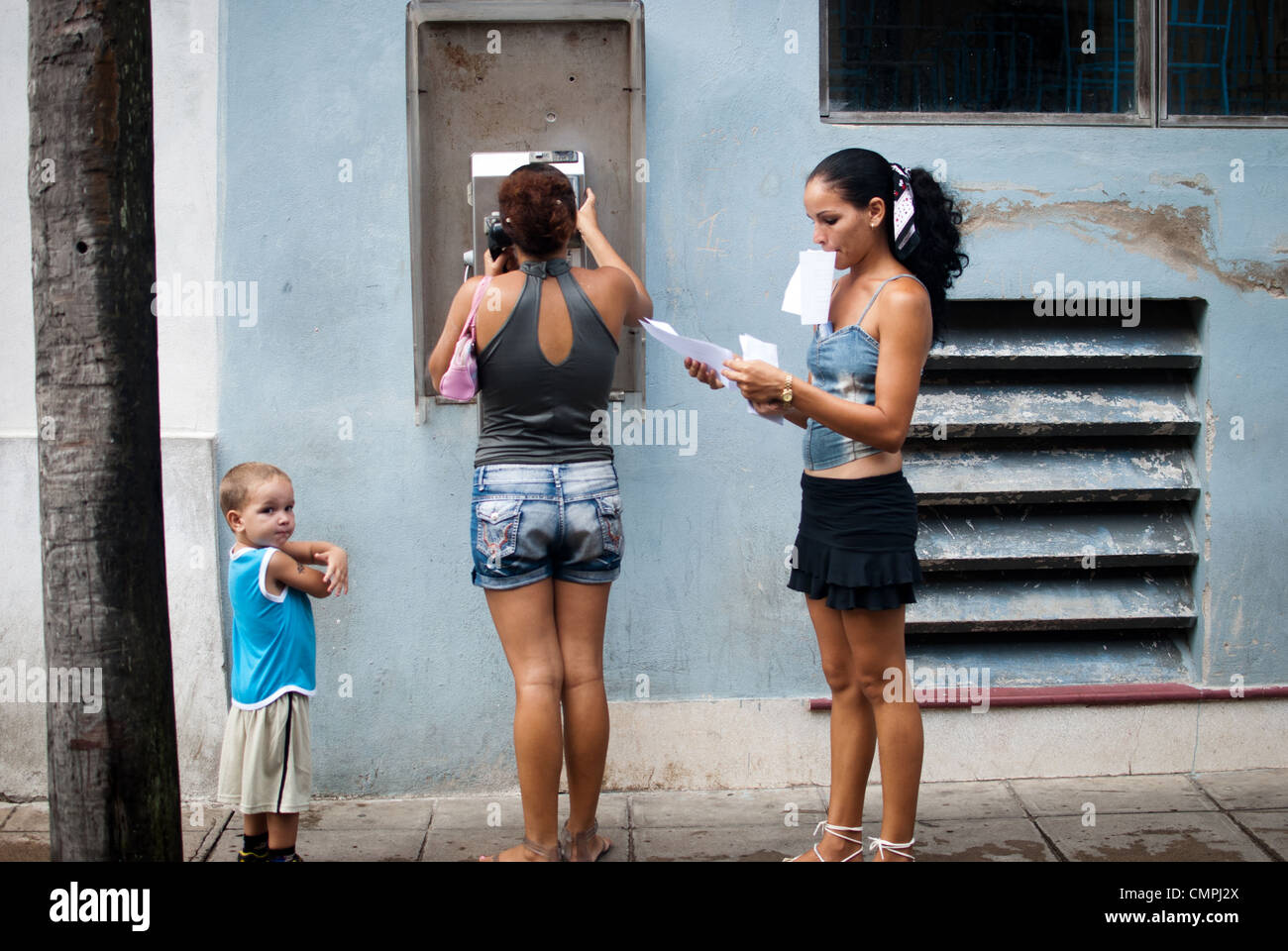 People using a  public phone, lady holding important papers in her month and hands trying to sort them out, Cuba - Stock Image