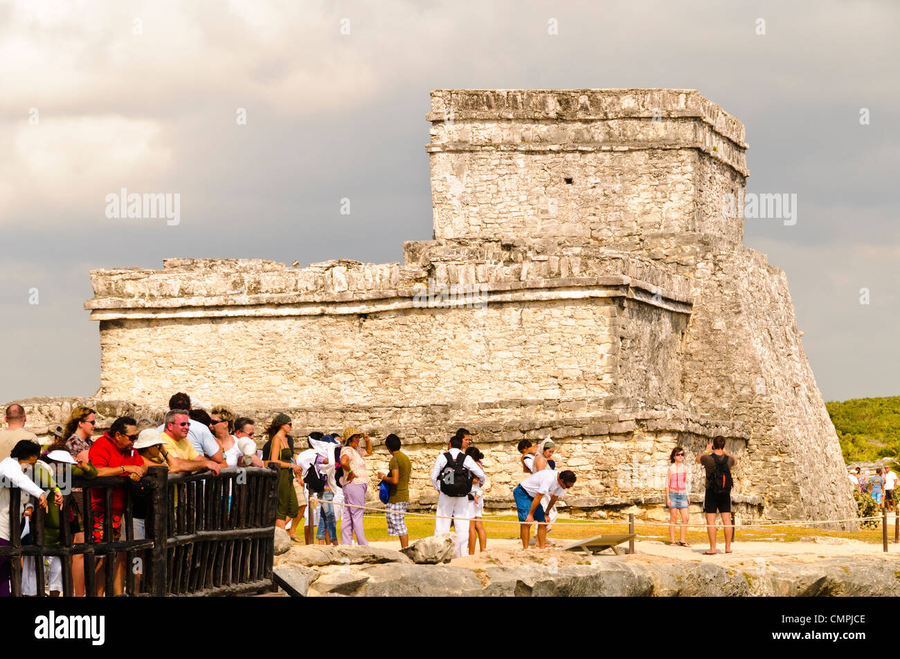 Tourists at the ruins of the Maya civilization city at Tulum look out over the Caribbean sea with El Castillo in - Stock Image
