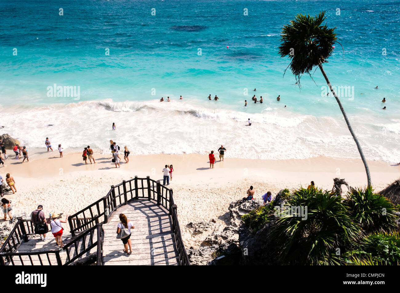 TULUM, Mexico - People swimming in the small surf of the Caribbean Sea from one of the beautiful white, sandy beaches - Stock Image