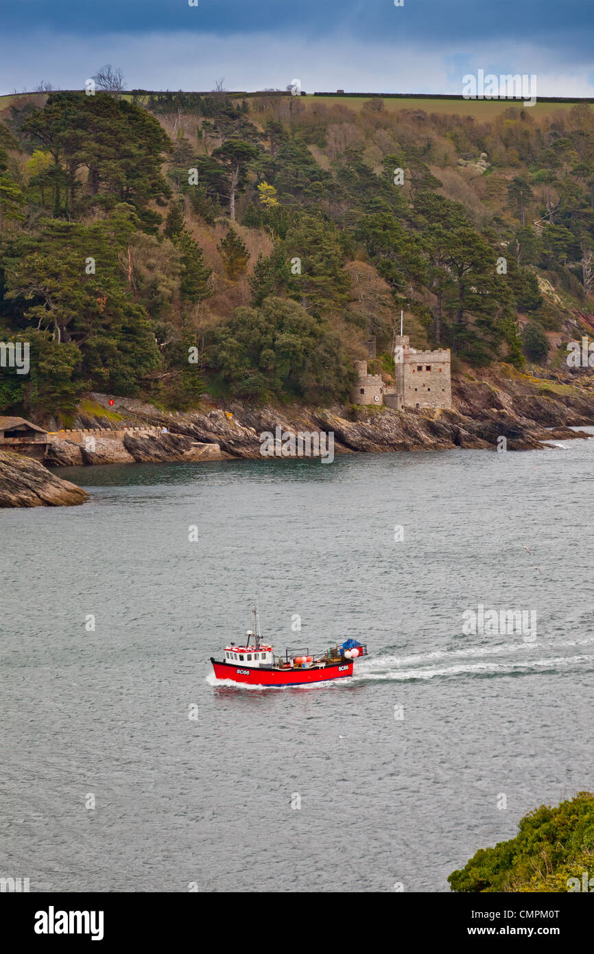 A small fishing boat passes Kingswear Castle guarding the entrance to the River Dart, Devon, England, UK - Stock Image