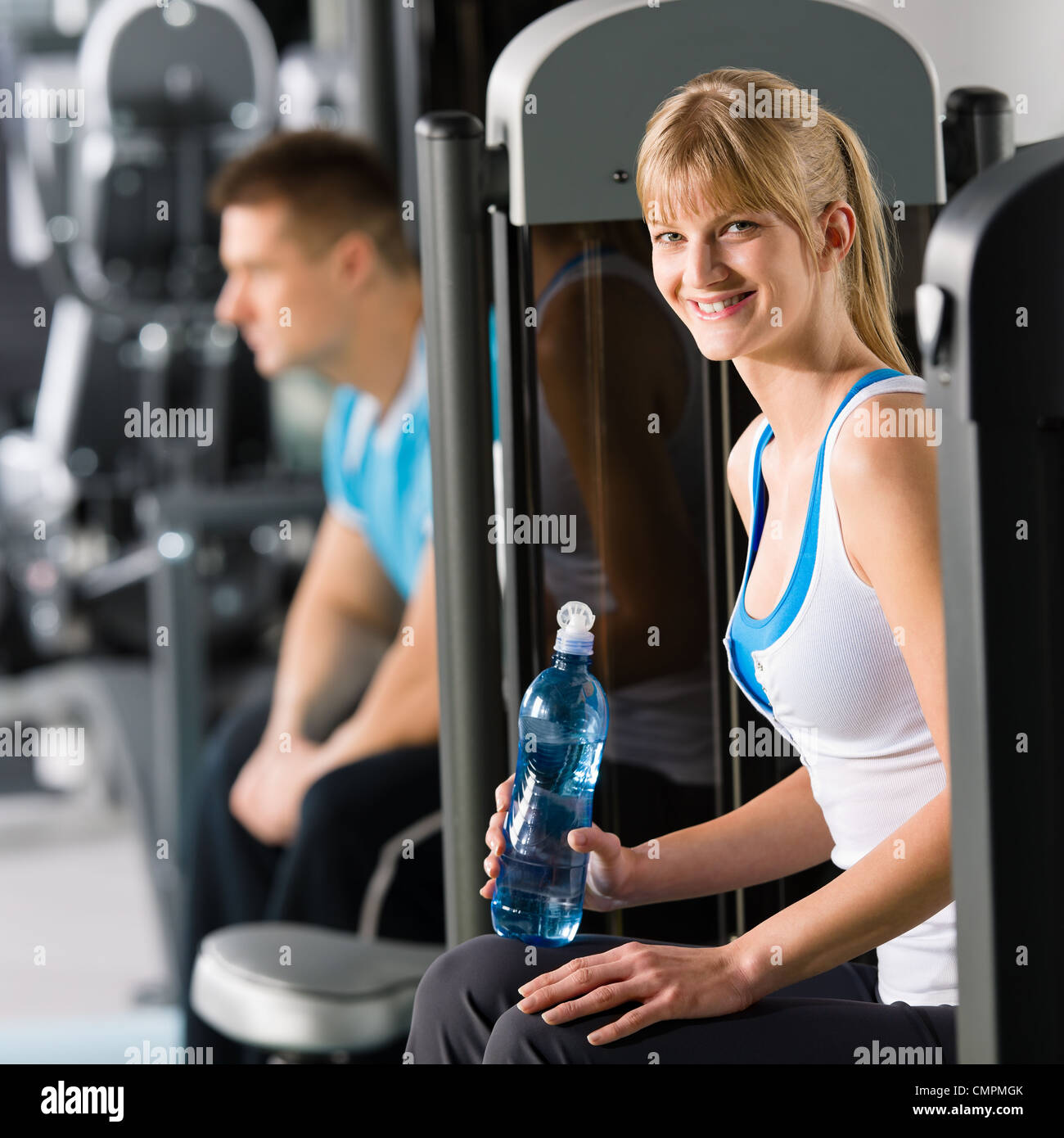 At the fitness center young woman relax on exercise machine - Stock Image