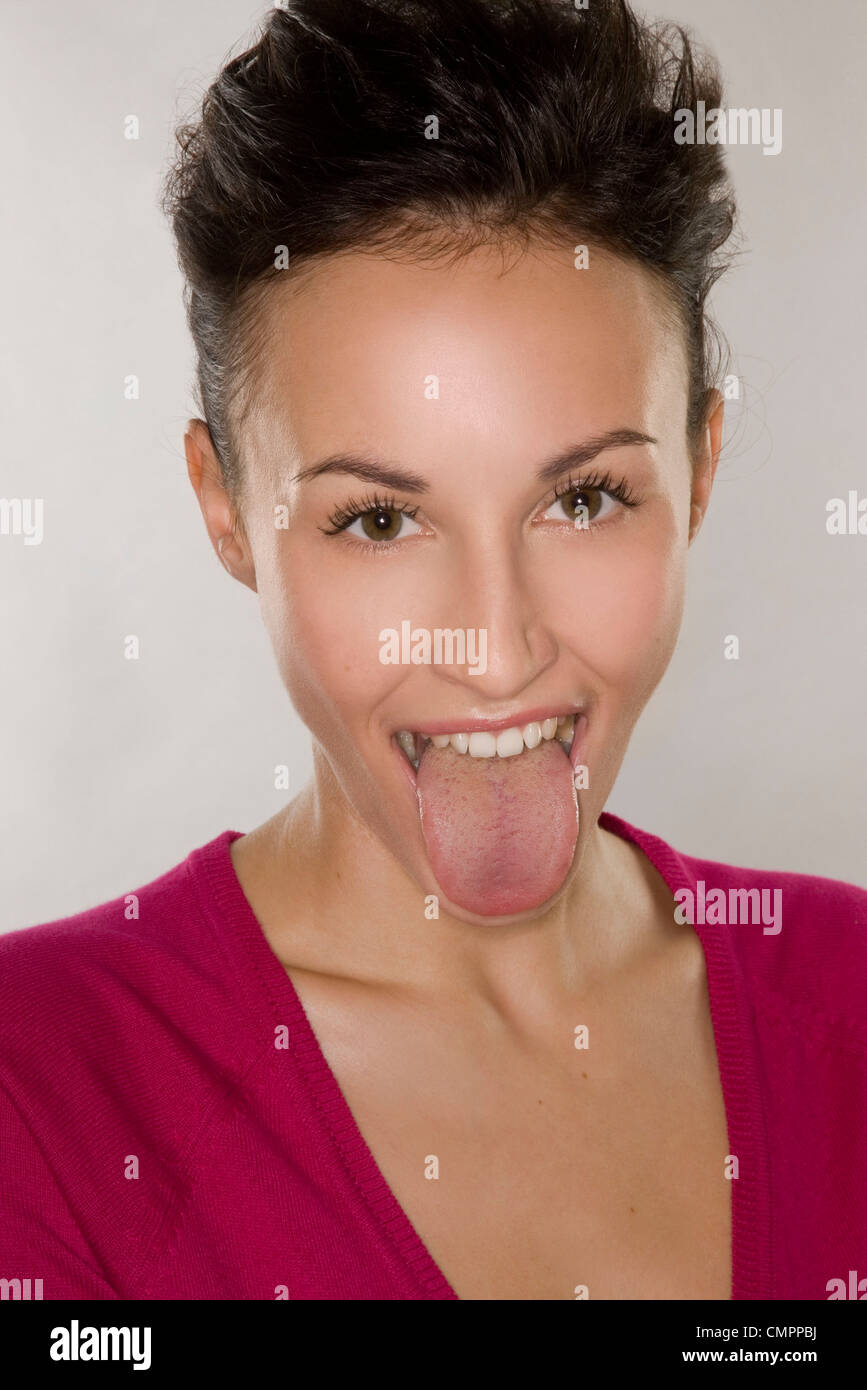Woman poking tongue out - Stock Image