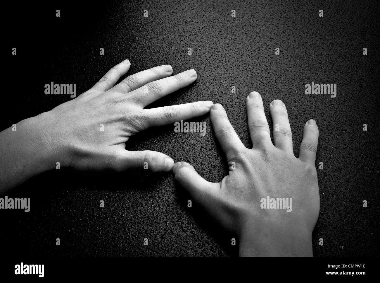 Two hands creating a heart shape on wet wood background Stock Photo