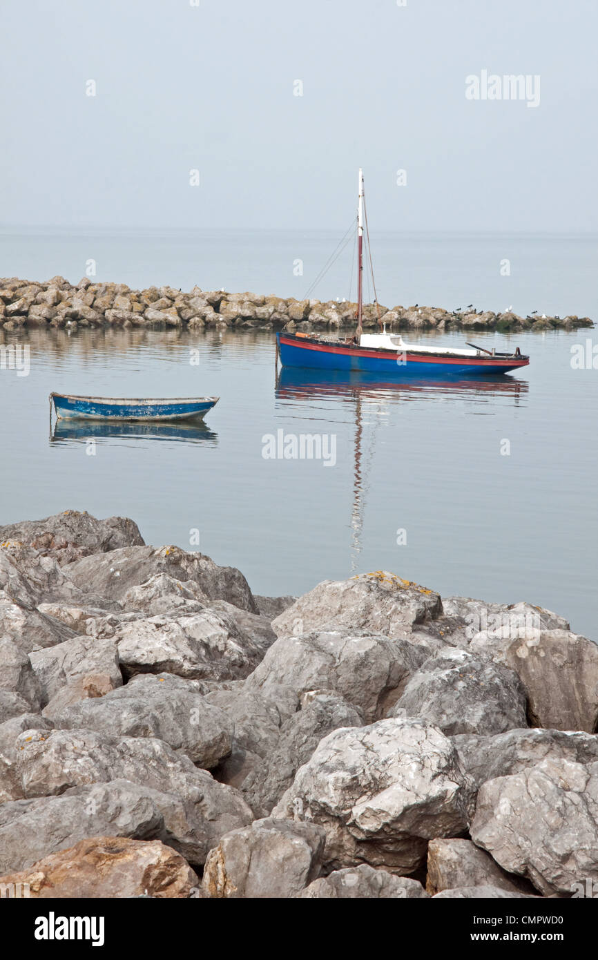 A Lancashire Nobby traditional inshore fishing boat, and a dinghy, moored at high tide on a calm day  at Morecambe, - Stock Image