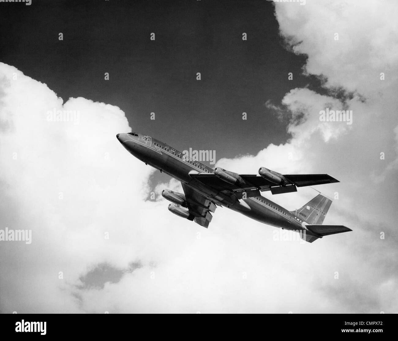 1960s AMERICAN AIRLINES A-707 JET ASCENDING THROUGH CLOUDS - Stock Image