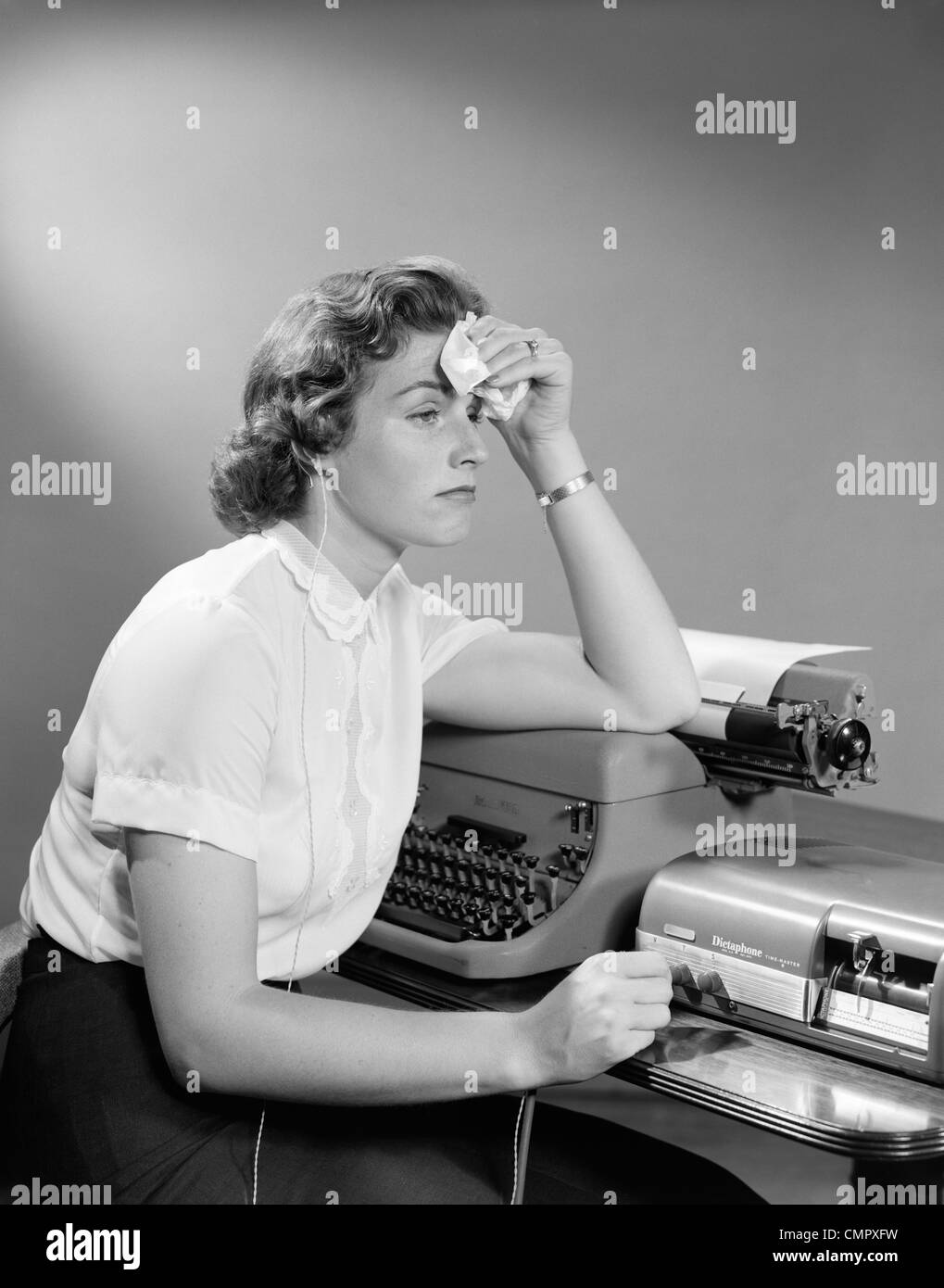 1950s AILING WOMAN SECRETARY SITTING AT DESK WITH TYPEWRITER AND DICTATION MACHINE HOLDING HANDKERCHIEF TO FOREHEAD - Stock Image