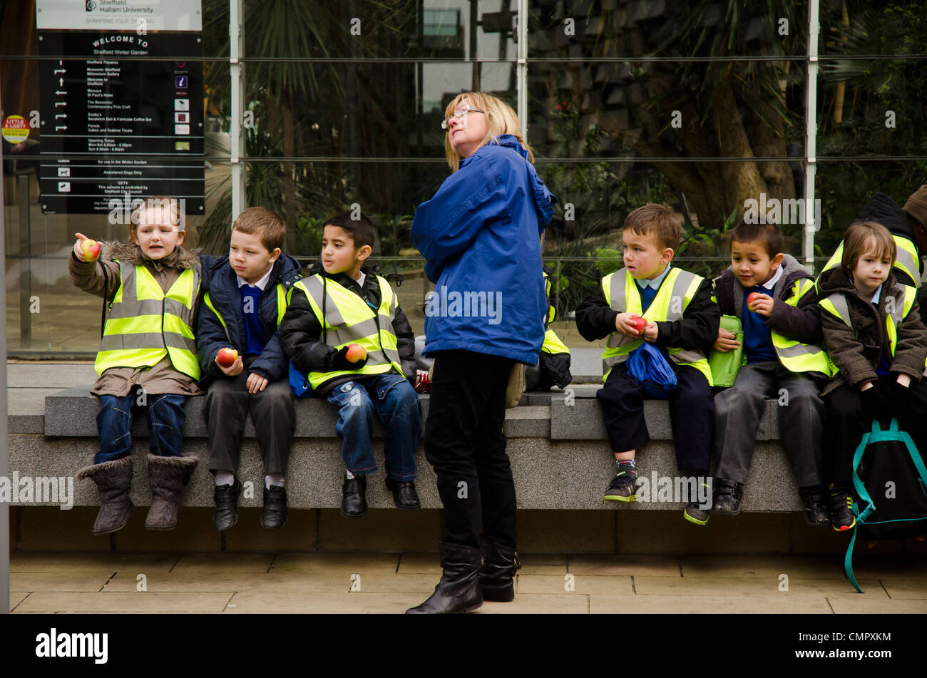 Class of young schoolchildren on excursion in Sheffield, UK. Note they're all eating apples, not junk food. Stock Photo