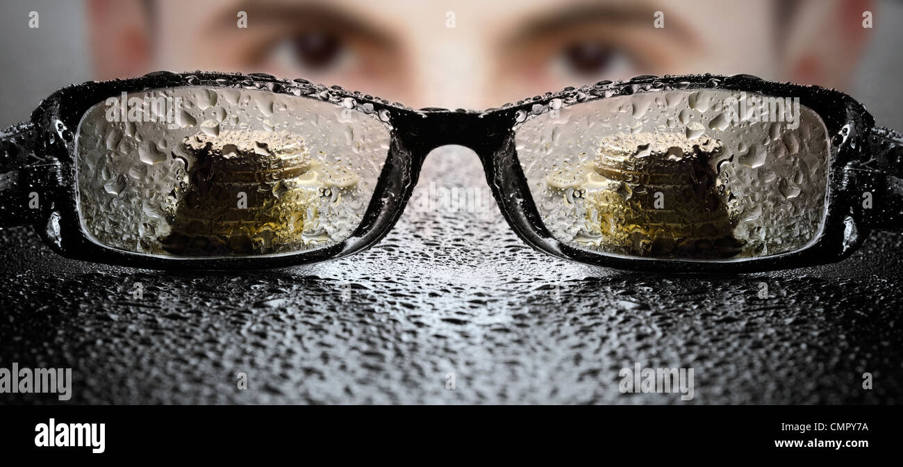 Young businessman looking at glasses - Stock Image