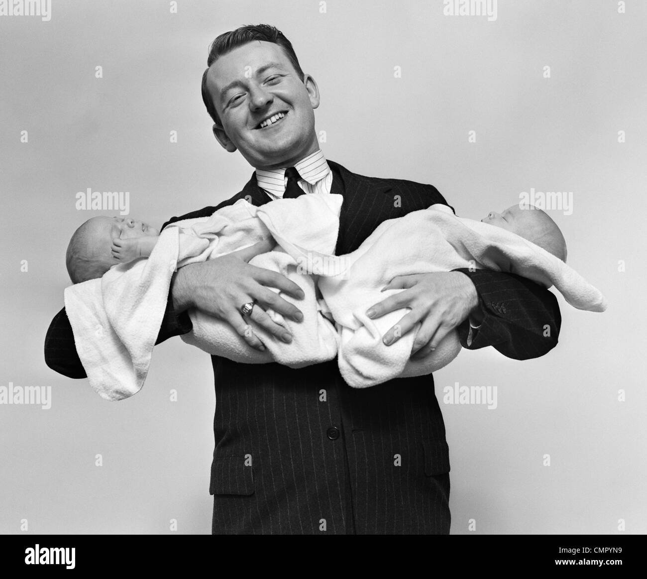 1930s PROUD FATHER SMILING PROUDLY HOLDING TWIN BABIES - Stock Image
