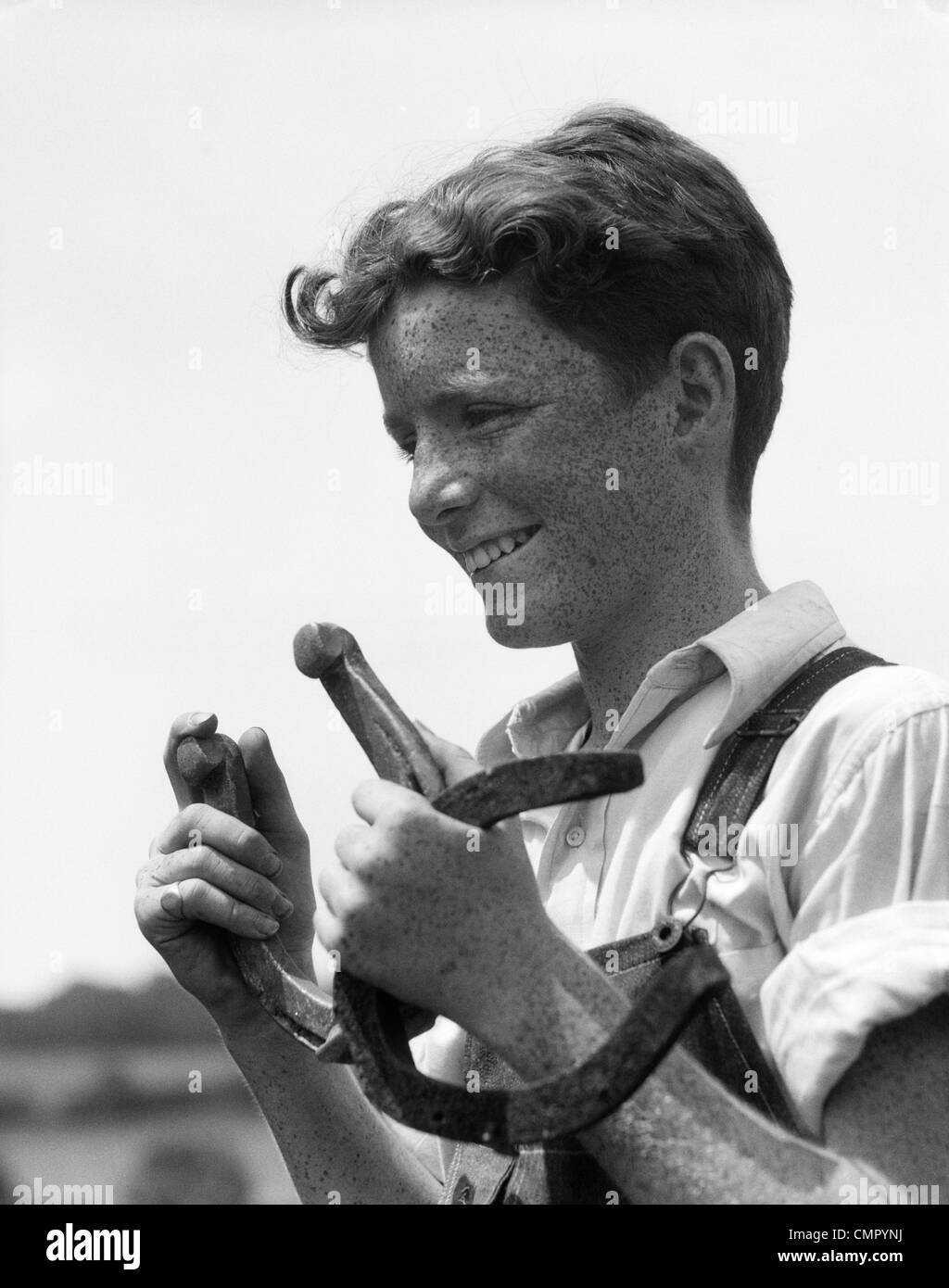 1930s CLOSE-UP OF SMILING FRECKLE-FACED BOY IN OVERALLS HOLDING TWO PITCHING HORSESHOES - Stock Image
