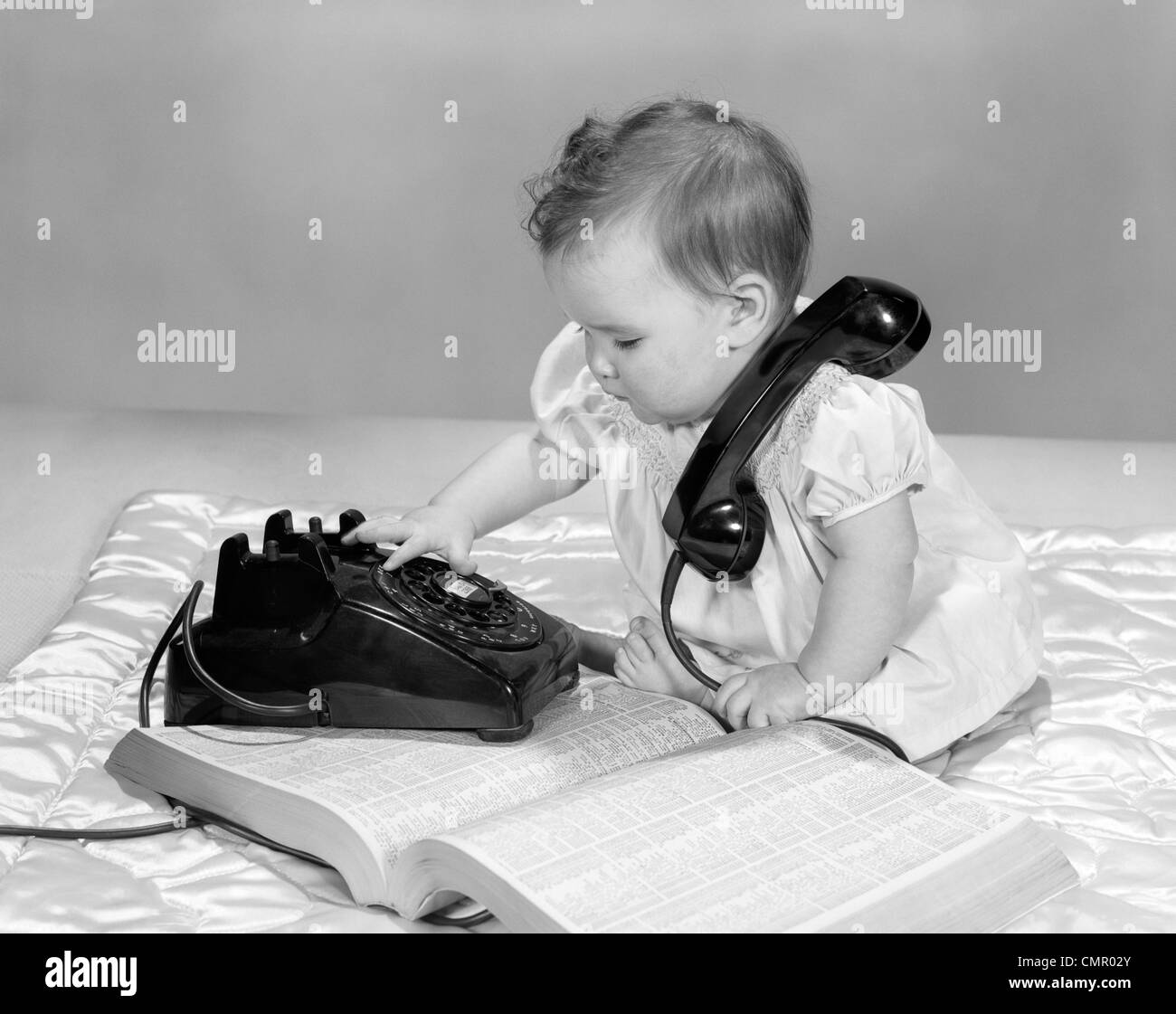 1960s BABY GIRL WITH TELEPHONE BOOK DIALING ROTARY TELEPHONE - Stock Image