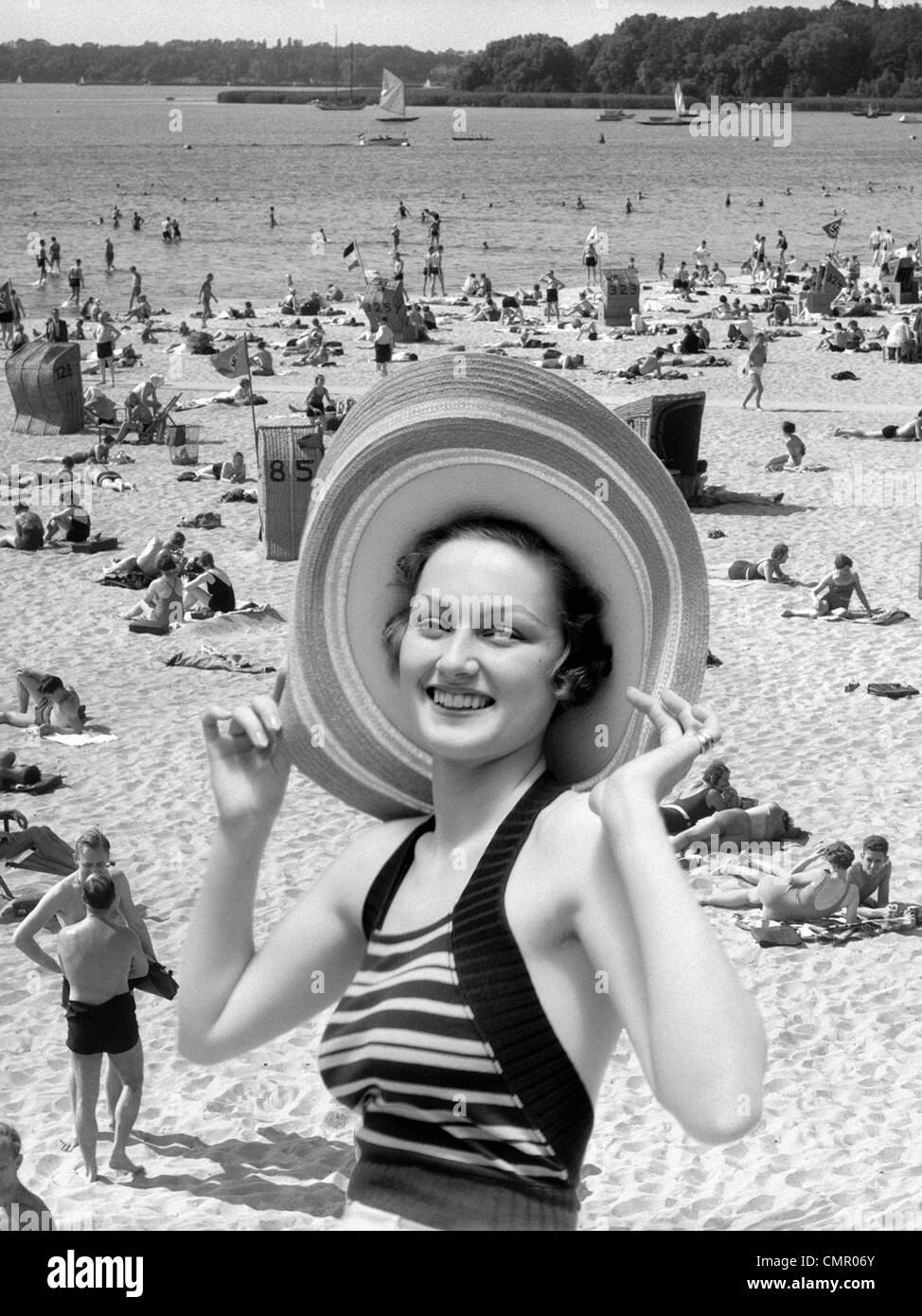 1930s VACATION MONTAGE PORTRAIT SMILING WOMAN IN BATHING SUIT WEARING LARGE STRAW HAT AND SCENE OF CROWDED BEACH - Stock Image
