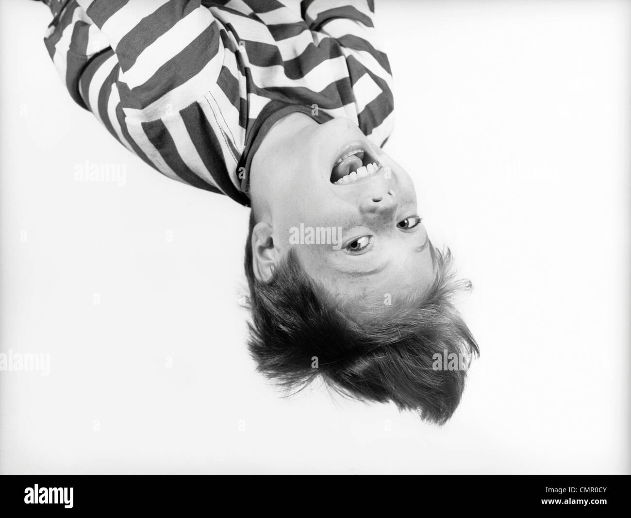 1950s BOY IN STRIPED T-SHIRT HANGING UPSIDE-DOWN - Stock Image