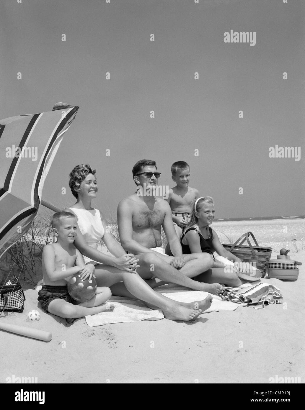 1960s FAMILY PORTRAIT MOTHER FATHER DAUGHTER AND TWO SONS SITTING ON BEACH UNDER UMBRELLA - Stock Image