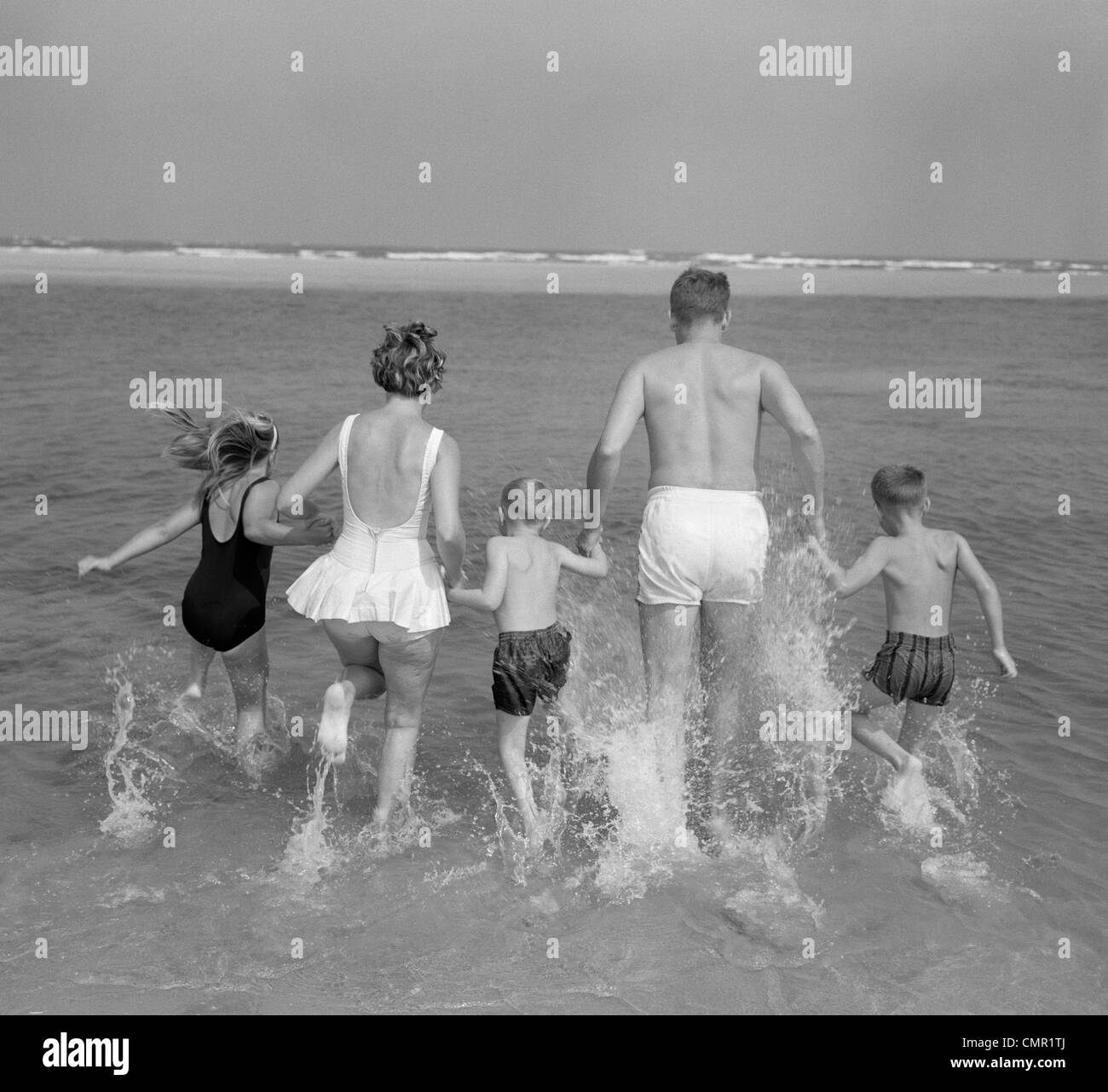 1960s BACK VIEW OF FAMILY OF 5 HOLDING HANDS RUNNING INTO OCEAN - Stock Image