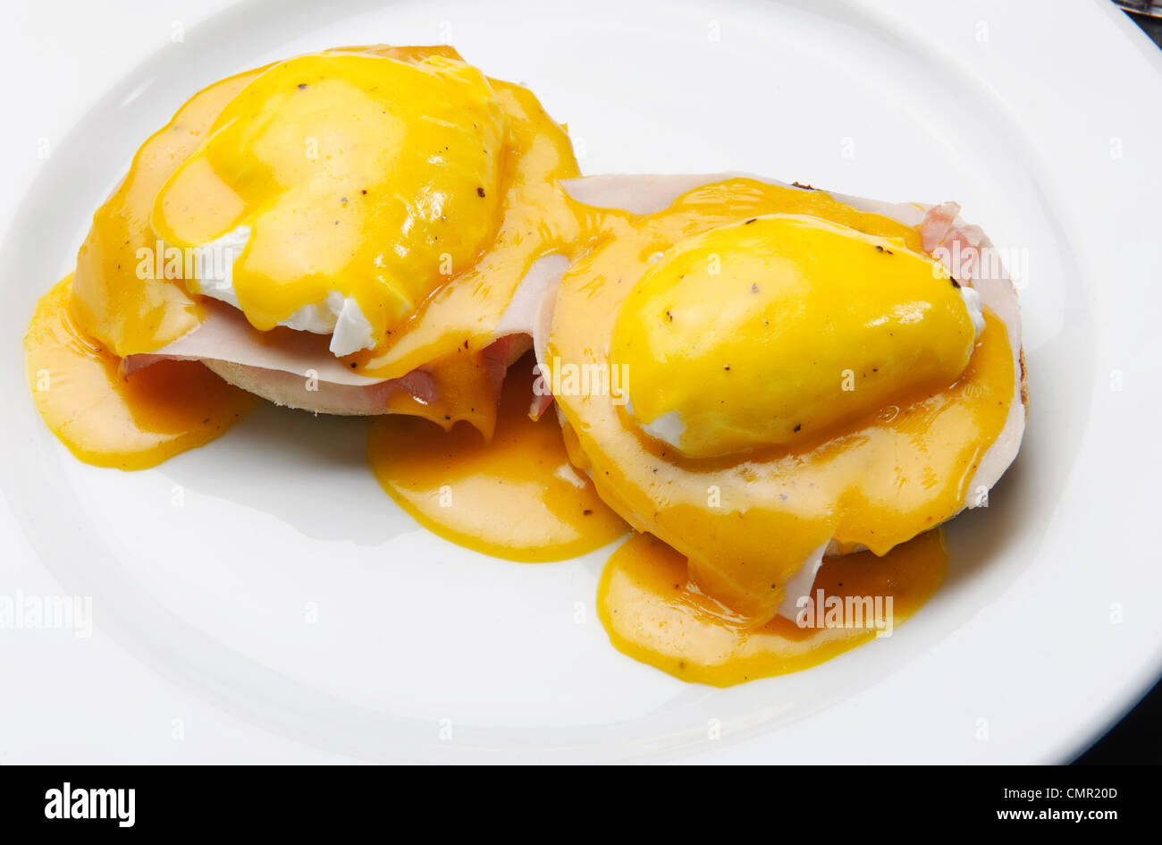 Eggs Benedict is a dish of two halves of an English muffin, topped with ham or bacon, poached eggs and Hollandaise - Stock Image