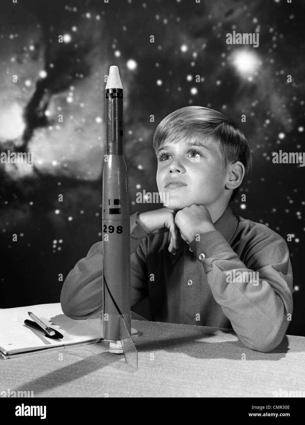 1960s BOY WITH MODEL ROCKET AND OUTER SPACE BACKGROUND - Stock Image