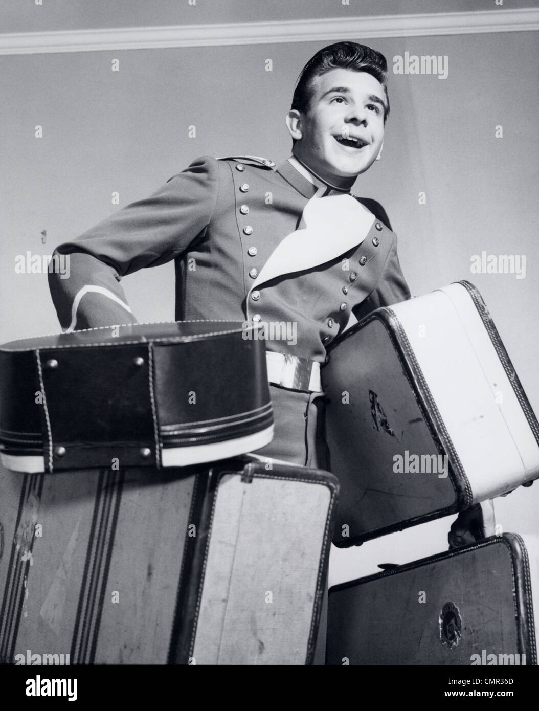 1950s SMILING BELLBOY CARRYING FOUR BAGS OF LUGGAGE - Stock Image