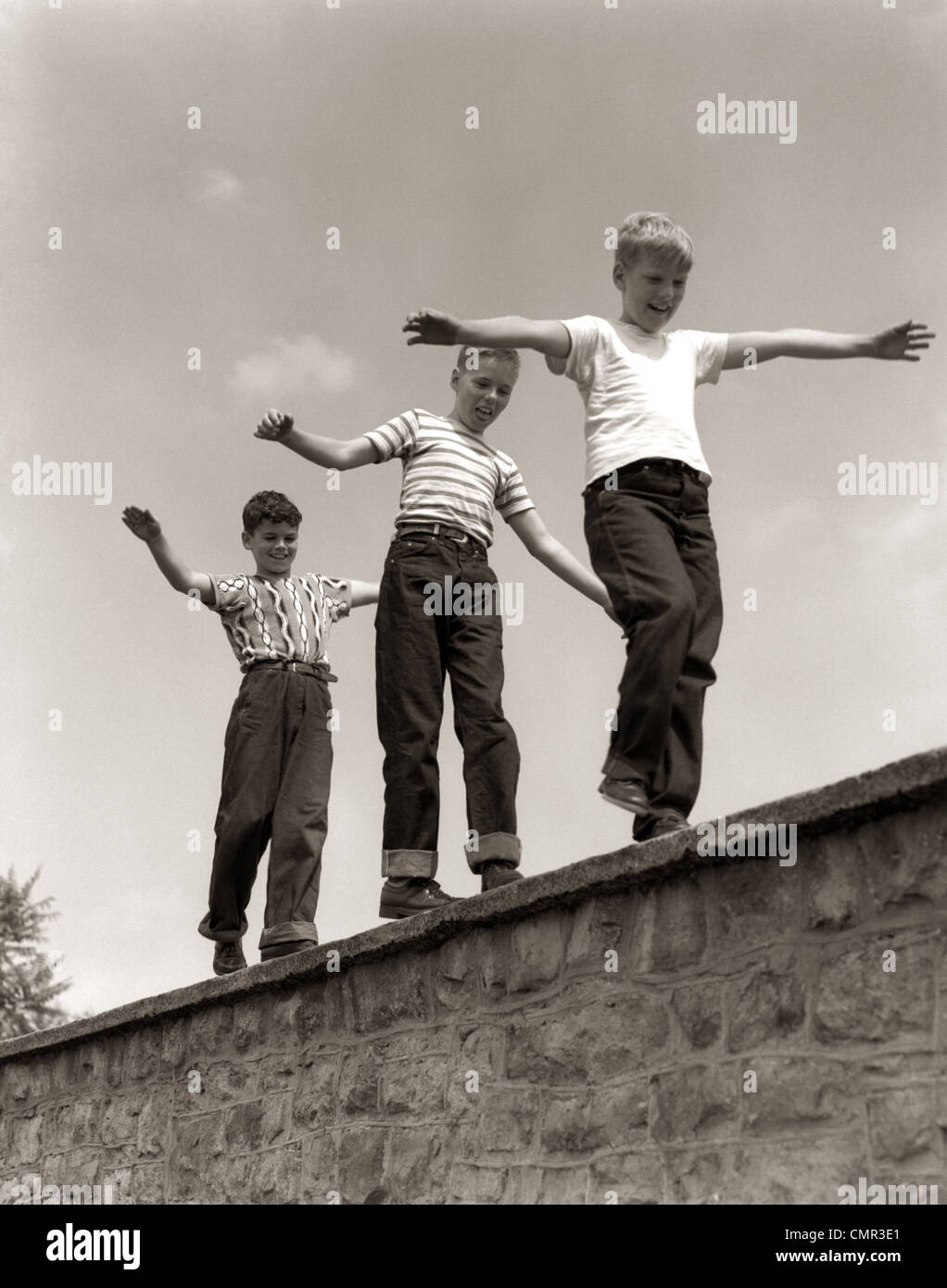 1950s THREE LAUGHING BOYS WALKING ON TOP OF STONE WALL ARMS OUT BALANCING PLAYING FOLLOW THE LEADER - Stock Image