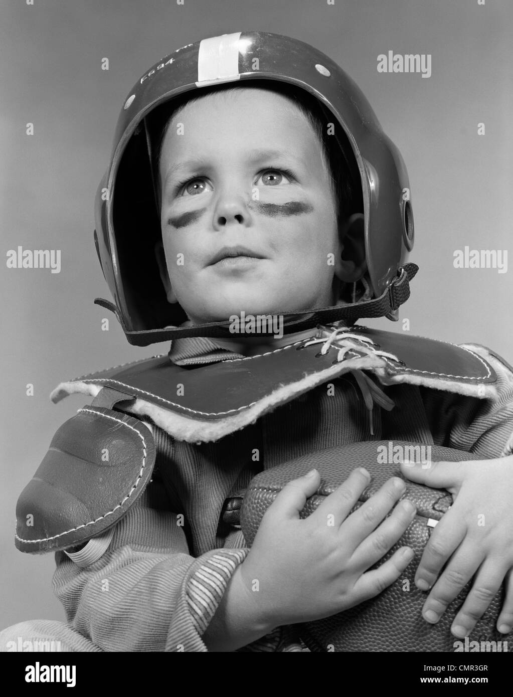 1950s PORTRAIT OF BOY IN HELMET & SHOULDER PADS WEARING GREASE PAINT UNDER EYES & HOLDING FOOTBALL - Stock Image