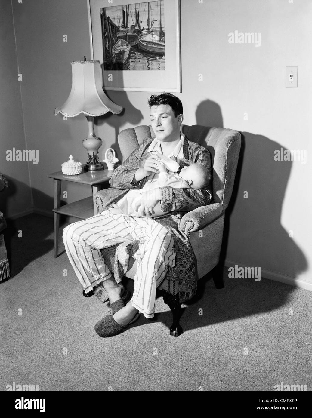 1950s TIRED FATHER GIVING BABY BOTTLE AT NIGHTTIME FEEDING - Stock Image
