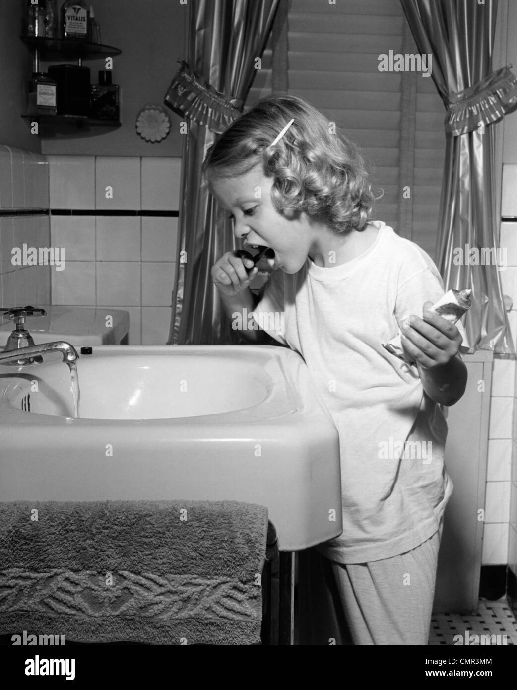 1950s Little Blond Girl In Pajamas Standing At Bathroom Sink