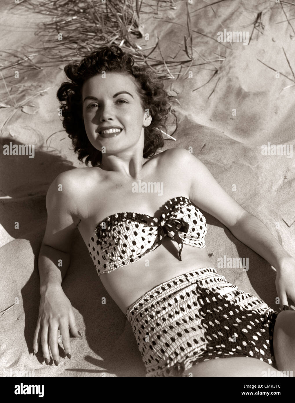 1950s SMILING BRUNETTE WOMAN WEAR POLKA DOT TWO PIECE BATHING SUIT LAYING ON SAND - Stock Image