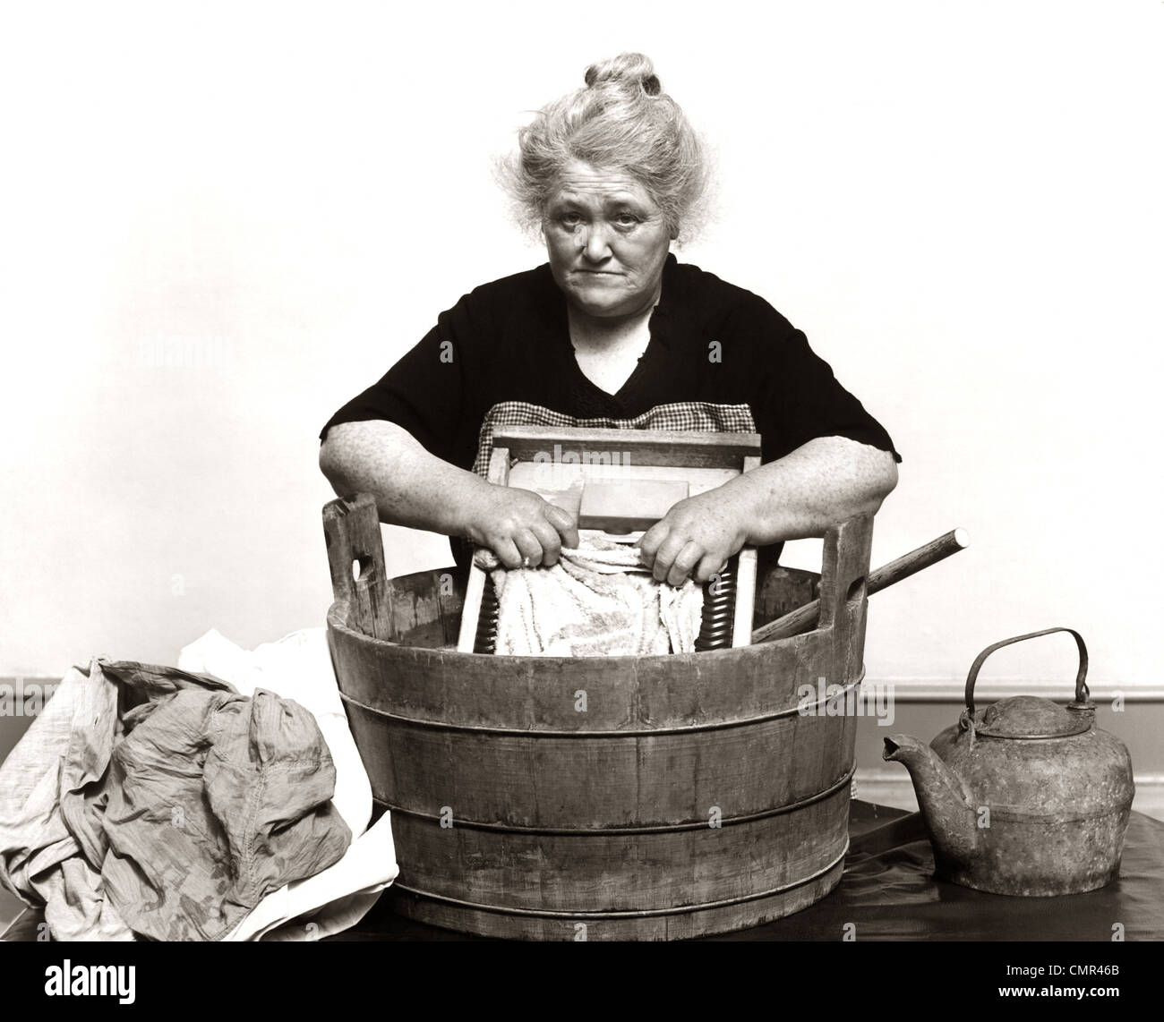1920s 1930s 1940s SENIOR WOMAN WASHING CLOTHES IN OLD FASHIONED WOODEN TUB AND WASHBOARD Stock Photo