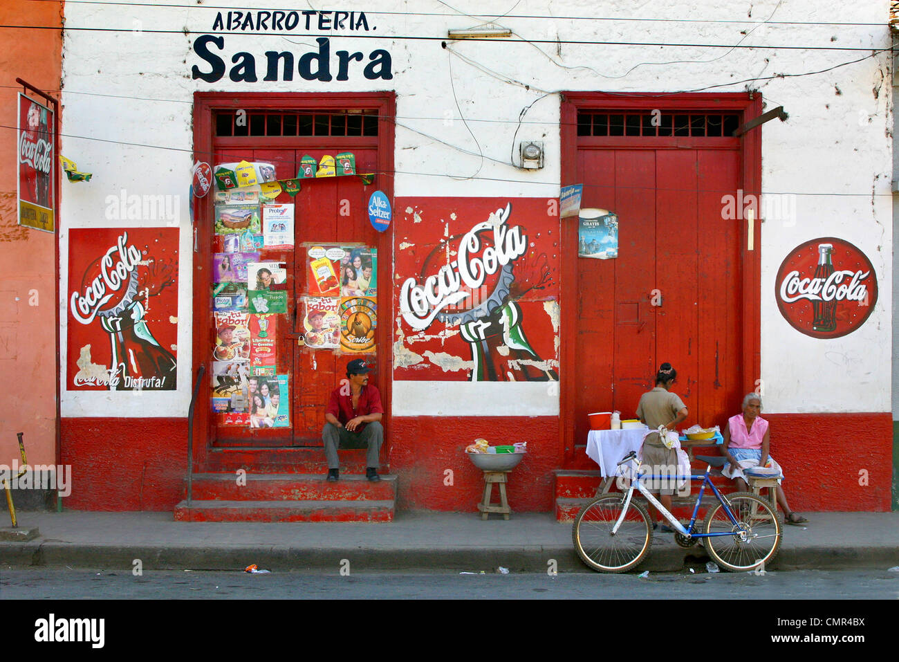 Leon, Nicaragua, street scene with coca cola signs and advertisements and posters stuck on red doors. - Stock Image