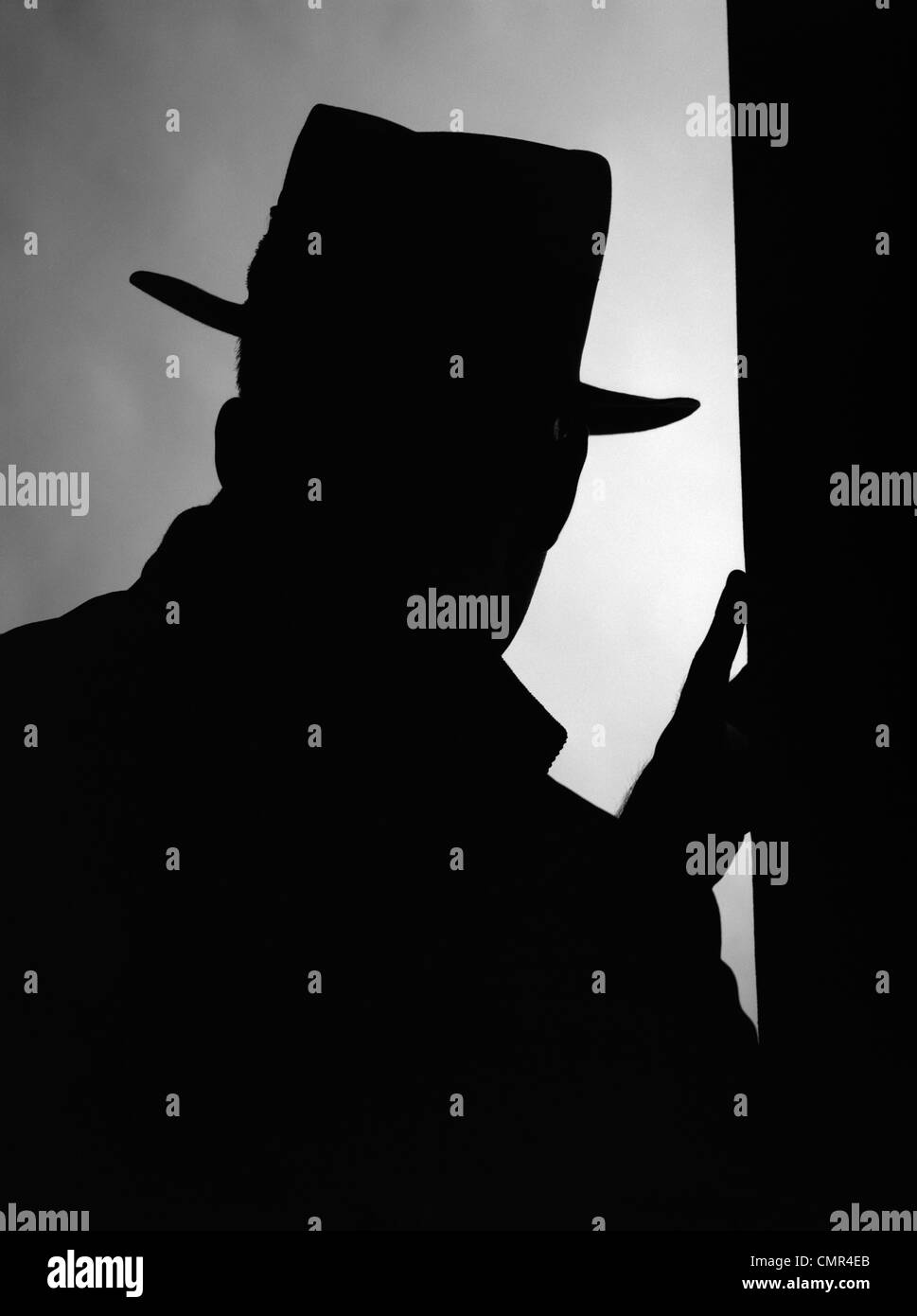 1950s SILHOUETTE OF MAN INTRUDER IN HAT AND COAT WITH ONE HAND ON A DOOR FRAME - Stock Image