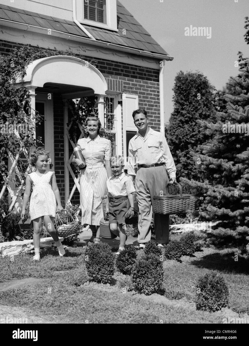 1940s 1950s FAMILY OF FOUR WALKING OUT OF HOUSE CARRYING PICNIC BASKETS THERMOS & JUG - Stock Image